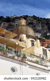 The dome of Chiesa di Santa Maria Assunta in front of a steep hillside, Positano, Italy