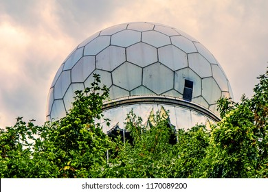 "Dome of a deserted and dilapidated station on the ""Teufelsberg"" (Devil Hill) in Berlin, Germany, in front of sunlit clouds. In the dome were until 1999 antennas and radars housed."
