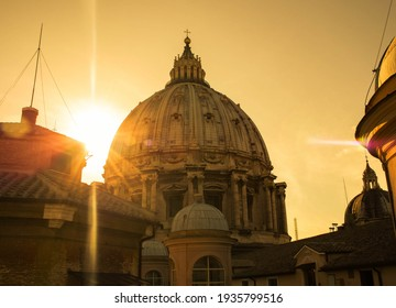Dome, roof of St Peter in the Vatican, Rome, surrounded by the rays of the sun at sunset