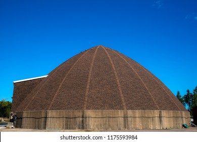 A dome shaped storage building. The building is for salt and sand that is used on highways during the winter. Blue sky above.