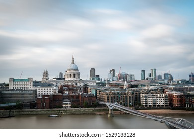 Dome of St. Pauls Cathedral and modern skyscrapers of The City of London as seen from the South shore of the river Thames on a cloudy Summer day. Long exposure.