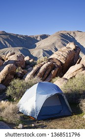 dome tent set up in the desert by rocks