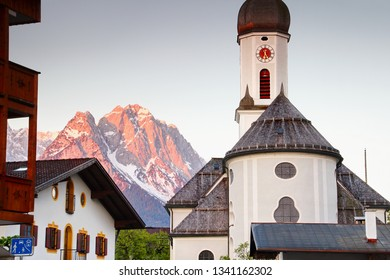 Domed parish church St Martin in historic center of resort town Garmisch-Partenkirchen with Waxenstein and Zugspitze peaks in red morning light, Wetterstein range Bavarian Alps Bayern Germany Europe