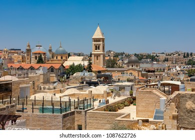 Domes and belfries among typical  stone buildings and rooftops under blue sky in Old City of Jerusalem, Israel.