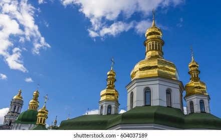 Domes of Kiev Pechersk Lavra against the background of a cloudy sky.