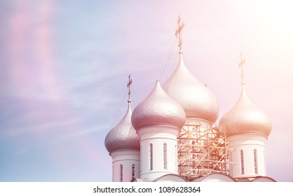 Domes of a religious building. Crosses on the domes of the church. Cathedral with silver domes against the sky