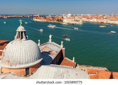 Domes of San Giorgio Maggiore church overlooking Grand canal and with boats and city skyline in Venice, Italy.