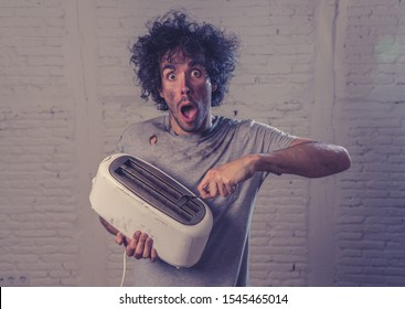 Domestic accidents and electricity danger. Young man electrocuted trying to get toast out of toaster with knife. Husband screaming as getting an electric shock with dirty burnt funny face expression.