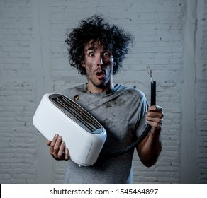 Domestic accidents and electricity dangers. Young man electrocuted trying to fix a toaster. Husband with dirty burnt funny face expression after getting an electric shock at home.