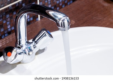 domestic bathroom faucet with pouring water. low water pressure. leaky tap concept. plumbing conceptual.