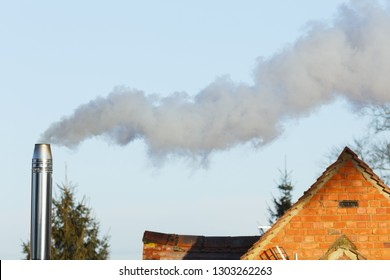 Domestic biomass chimney emitting smoke and pollutants into the environment