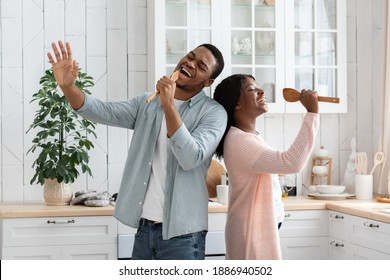 Domestic Concert. Playful African American Couple Having Fun In Kitchen, Singing And Dancing While Cooking Lunch At Home, Cheerful Black Millennial Spouses Using Spatulas As Microphones, Free Space