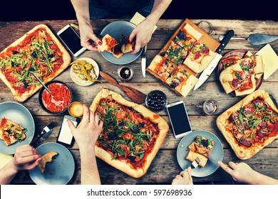 Domestic food and homemade pizza. Enjoying dinner with friends. Top view of group of people having dinner together while sitting at the rustic wooden table