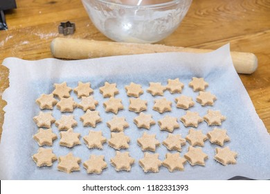 Domestic home baking: messy arrangement of star shaped cinnamon Christmas cookies on kitchen bench with cutter, rolling pin and mixing bowl in background