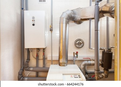 A domestic household boiler room with a new modern solid fuel boiler , heating electric warm water system and pipes