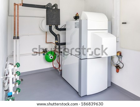 A domestic household boiler room with a new modern heating oil warm water system and pipes