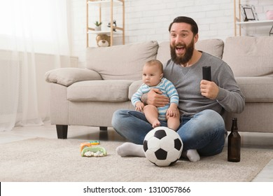 Domestic life of dad in paternity leave. Emotional man watching football game on tv, holding baby and drinking beer, free space