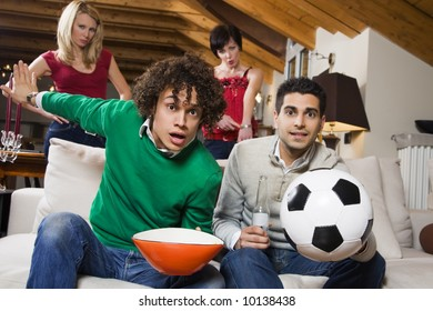domestic life: group of friends watch soccer on tv while girlfriends stand behind.