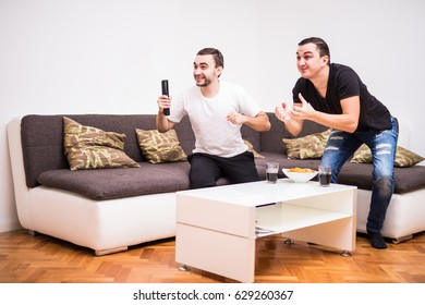 Domestic life: Two young men watching a football match on tv. Sport fans
