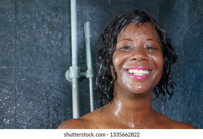 domestic lifestyle portrait of young happy and beautiful black African American woman smiling happy taking a shower at home bathroom washing her hair with shampoo in beauty and hygiene concept