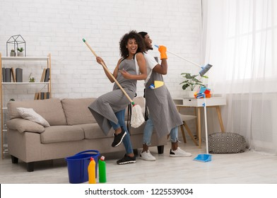 Domestic music band - black man and woman having fun during house cleaning, playing with mop and broom