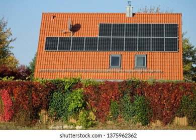 Domestic photovoltaic solar panels on a rural houses roof with autumn colours