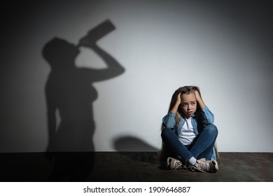 Domestic physical violence, abusing. Scared little caucasian girl, victim sitting close to white wall with shadow of angry threatening mother with alcohol addiction. Awareness of social problem.