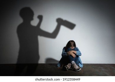 Domestic physical violence, abusing. Scared little caucasian girl, victim sitting close to white wall with shadow of angry threatening father with alcohol addiction. Awareness of social problem.