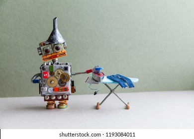 Domestic robot ironing jeans, green gray background. Robotic automation housework service concept. Copy space