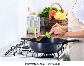 Domestic scene of anonymous woman cooking by the gas stove adding some broccoli