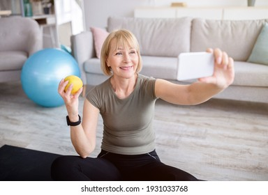 Domestic sports and healthy diet. Cheerful mature woman taking selfie with apple after home workout, indoors. Positive senior lady making photo of herself, taking care of her body and nutrition