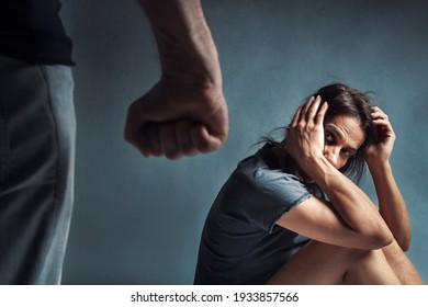 Domestic violence or abuse concept: Frightened helpless woman with black swollen eye trying to protect herself while looking at the angry husband's fist in the foreground. Focus on woman.