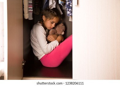 Domestic violence and abused concept. Unhappy and scared child hiding in the wardrobe and sitting there down in the mouth with Teddy in her hands