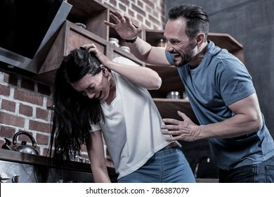Domestic violence. Angry drunk brutal man shouting at his wife and beating her while having a quarrel