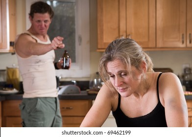domestic violence - battered woman looks depressed as beer-drinking man rages angrily behind her