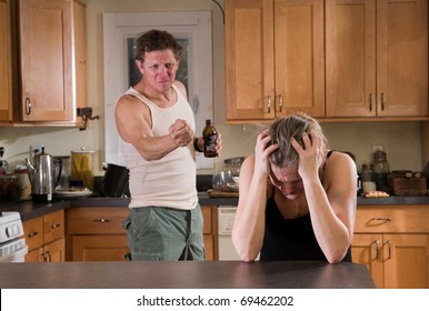 domestic violence - beer drinking man threatens his wife with fist
