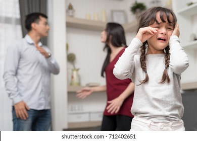 Domestic violence and Family conflict concept. Sadness little girl against blured of mother fighting father with quarrel at home. Setup studio shooting.