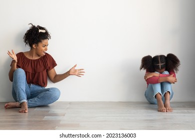 Domestic violence, kids abuse at home concept. Mad black lady abusive mother emotionally gesturing and shouting at her crying female kid, sitting together on floor over empty wall, copy space