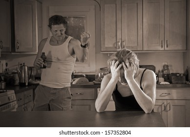 domestic violence with lighting effect - beer-drinking man threatens woman (with bruises)