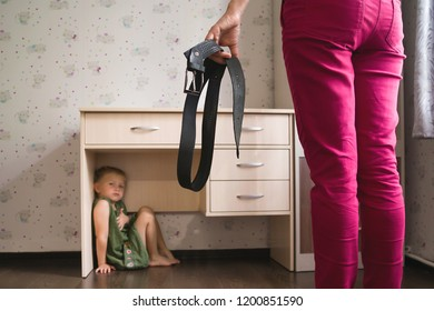 Domestic violence. Mother holding the belt in her hand to punish her small daughter. Scared child hiding under a table and sitting there terrified by physical punishment