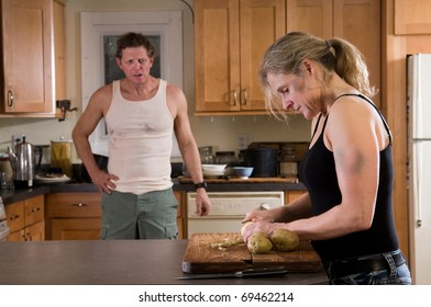 domestic violence - wide with bruises on arm and face peels potatoes while husband glowers at her