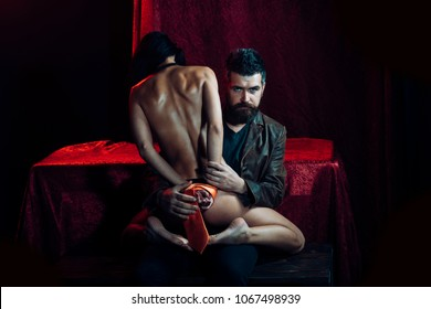 Dominance and submission, couple. Love, man and woman with tied hand. Couple in love, bdsm, bearded man and naked girl. Erotic games, sex, orgasm, girl and man. Sexy woman with tied hands, buttocks.