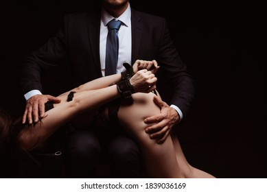 dominant man slaps a submissive girl in underwear on a sexy ass with his hand. Concept of hard BDSM sex