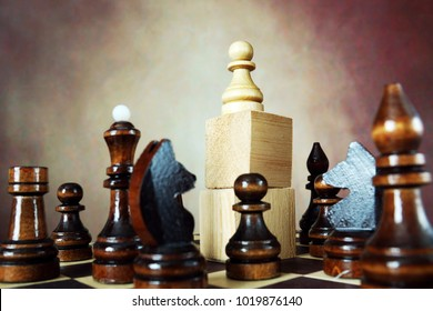 Domination. Concept with chess pieces. Chess pawn has an supremacy over enemy team because he stands on a high stand