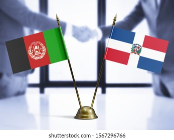 Dominican Republic and Afghanistan mini table flags on white wooden desk. Diplomatic background with men shaking hands, international relations and agreements.