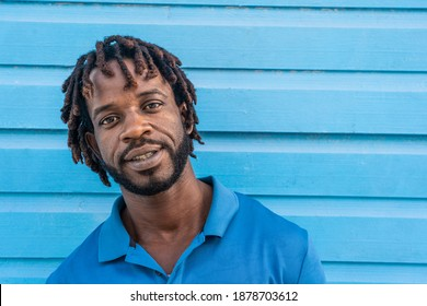 Dominican Republic. Close-up face of smiling young African American against blue wall. Portrait of a happy man. Dominican people.