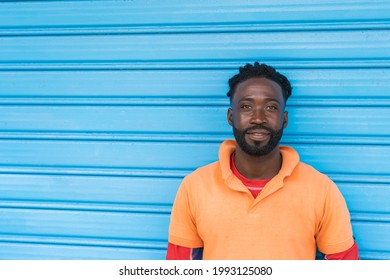 Dominican Republic. Close-up portrait of smiling young African American man against blue background. Dominican people.