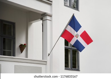 Dominican Republic flag. Dominican Republic flag hanging in front of the house. National flag waving on a home displaying on a pole on a front door of a building. Flag raised at a full staff.
