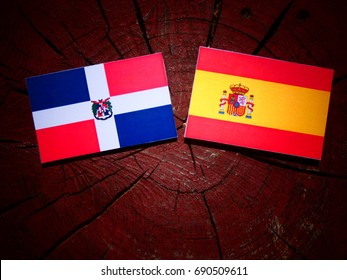 Dominican Republic flag with Spanish flag on a tree stump isolated