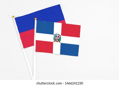 Dominican Republic and Haiti stick flags on white background. High quality fabric, miniature national flag. Peaceful global concept.White floor for copy space.